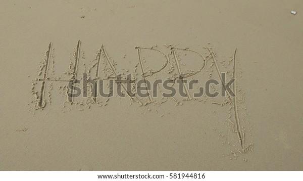 "Handwriting words ""HAPPY"" on sand of beach"