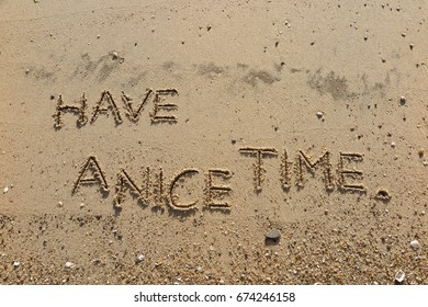 """Handwriting  words """"HAVE A NICE TIME."""" on sand of beach."""