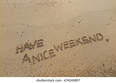 """Handwriting  words """"HAVE A NICE WEEKEND."""" on sand of beach."""