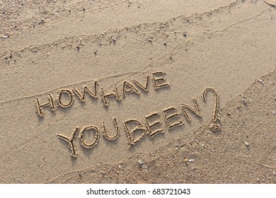 """Handwriting  words """"HOW HAVE YOU BEEN?"""" on sand of beach."""