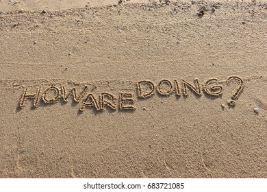 """Handwriting  words """"HOW ARE DOING?"""" on sand of beach."""
