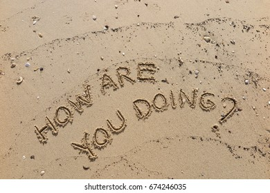 """Handwriting  words """"HOW ARE YOU DOING?"""" on sand of beach."""