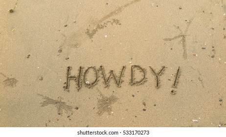 "Handwriting words ""HOWDY!"" on sand of beach"
