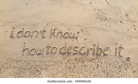 """Handwriting words """"I don't know how to describe it."""" on sand of beach"""