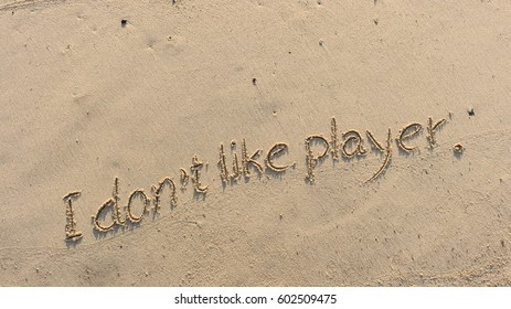 """Handwriting words """"I don't like player."""" on sand of beach"""