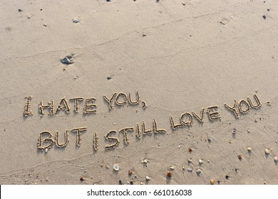 """Handwriting  words """"I HATE YOU, BUT I STILL LOVE YOU."""" on sand of beach."""