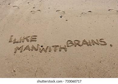 "Handwriting  words ""I LIKE MAN WITH BRAINS."" on sand of beach."