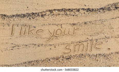 """Handwriting words """"I like your smile"""" on sand of beach"""