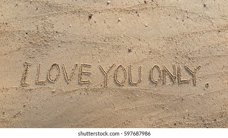 """Handwriting words """"I LOVE YOU ONLY."""" on sand of beach"""