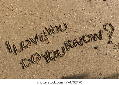 """Handwriting  words """"I LOVE YOU DO YOU KNOW?"""" on sand of beach."""