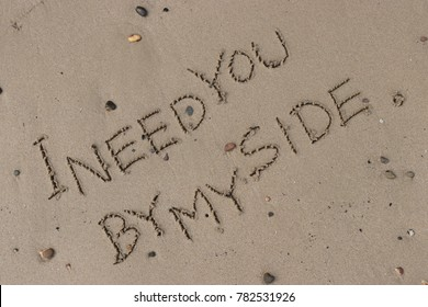 """Handwriting  words """"I NEED YOU BY MY SIDE."""" on sand of beach."""