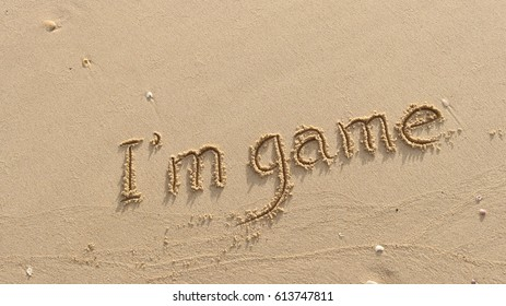 "Handwriting words ""I'm game"" on sand of beach"