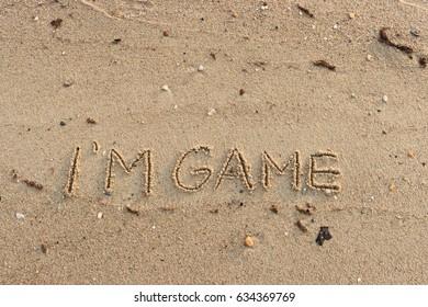 "Handwriting  words ""I'M GAME"" on sand of beach."