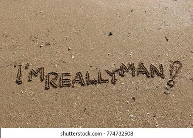 "Handwriting  words ""I'M REALLY MAN!"" on sand of beach."