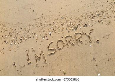 "Handwriting  words ""I'M SORRY."" on sand of beach."