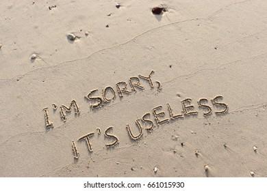 "Handwriting  words ""I'M SORRY, IT'S USELESS."" on sand of beach."