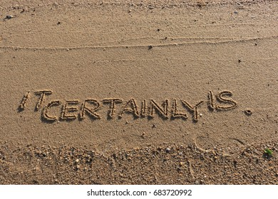 """Handwriting  words """"IT CERTAINLY IS."""" on sand of beach."""