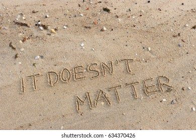 """Handwriting  words """"IT DOESN'T MATTER"""" on sand of beach."""