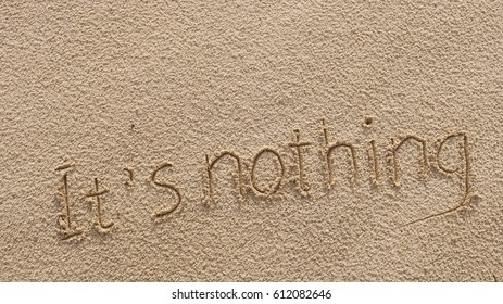 "Handwriting words ""It's nothing"" on sand of beach"