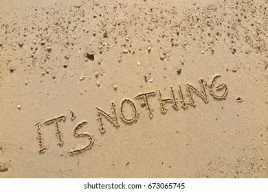 """Handwriting  words """"IT'S NOTHING."""" on sand of beach."""