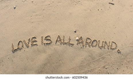 "Handwriting words ""LOVE IS ALL AROUND."" on sand of beach"