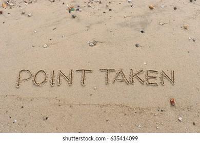 "Handwriting  words ""POINT TAKEN"" on sand of beach."