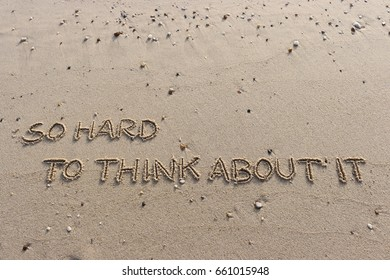 """Handwriting  words """"SO HARD TO THINK ABOUT IT"""" on sand of beach."""