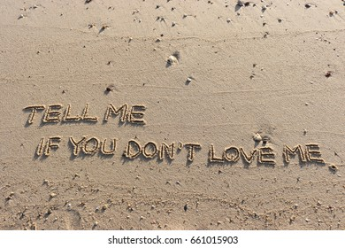 """Handwriting  words """"TELL ME IF YOU DON'T LOVE ME."""" on sand of beach."""