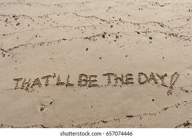 """Handwriting  words """"THAT'LL BE THE DAY!"""" on sand of beach."""