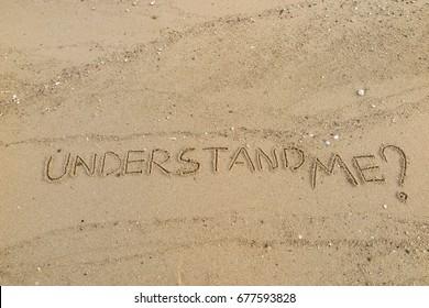 "Handwriting  words ""UNDERSTAND ME?"" on sand of beach."
