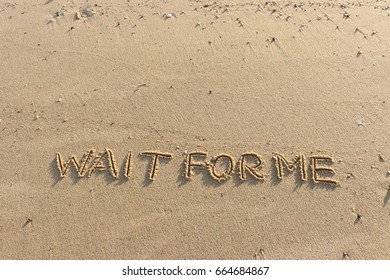 """Handwriting  words """"WAIT FOR ME"""" on sand of beach."""