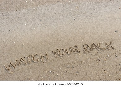 """Handwriting  words """"WATCH YOUR BACK"""" on sand of beach."""
