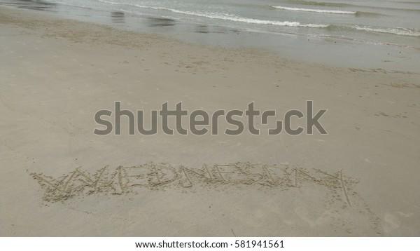 "Handwriting words ""WEDNESDAY"" on sand of beach"