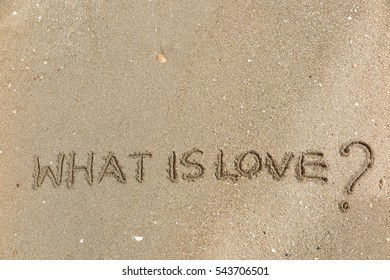 """Handwriting words """"WHAT IS LOVE?"""" on sand of beach"""