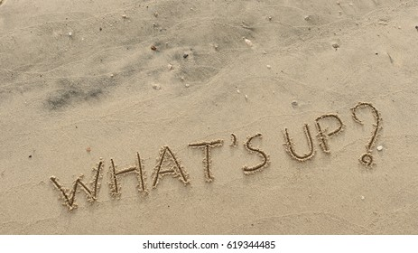"""Handwriting  words """"WHAT'S UP?"""" on sand of beach."""