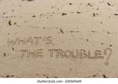 """Handwriting  words """"WHAT'S THE TROUBLE?"""" on sand of beach."""