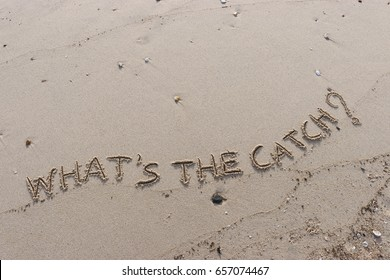 """Handwriting  words """"WHAT'S THE CATCH?"""" on sand of beach."""