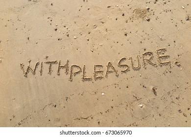 "Handwriting  words ""WITH PLEASURE."" on sand of beach."