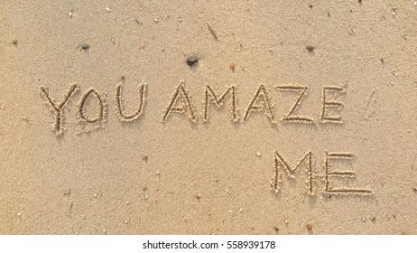 "Handwriting words ""YOU AMAZE ME"" on sand of beach"