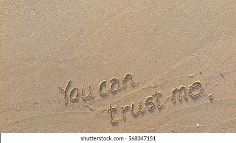 "Handwriting words ""You can trust me."" on sand of beach"