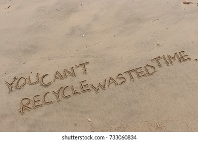 """Handwriting  words """"YOU CAN'T RECYCLE WASTED TIME."""" on sand of beach."""