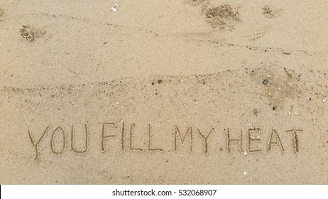 """Handwriting words """"YOU FILL MY HEAT"""" on sand of beach"""