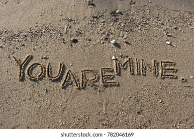 """Handwriting  words """"YOU ARE MINE."""" on sand of beach."""