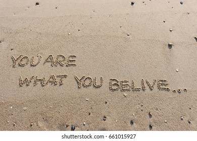 """Handwriting  words """"YOU ARE WHAT YOU BE LIVE."""" on sand of beach."""