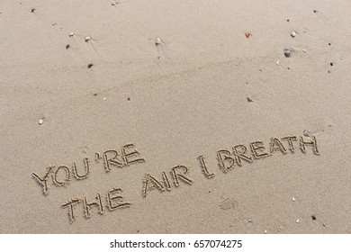 """Handwriting  words """"YOU'RE THE AIR I BREATH"""" on sand of beach."""