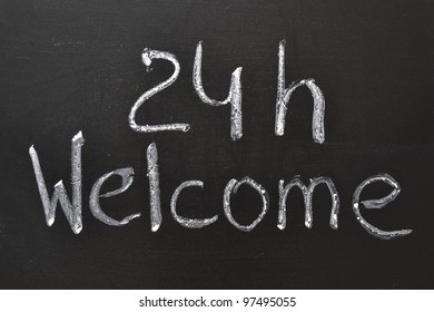 Handwritten 24 h Welcome sign on the blackboard