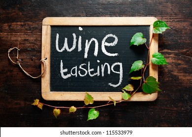 Handwritten decorative Wine tasting sign on a small rustic slate chalkboard with trailing leaves from a green creeper and dark textured wood background