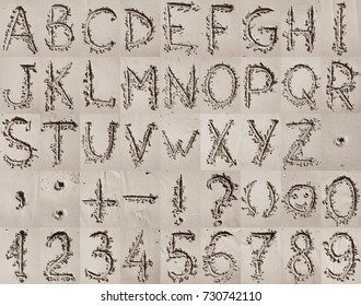 Handwritten English alphabet, numbers and mathematical symbols on the sand. Alphabet concept.
