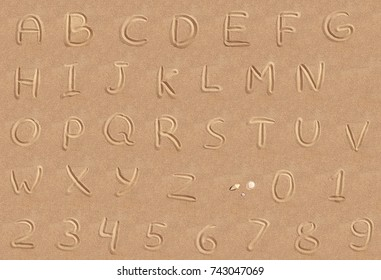 Handwritten font alphabet on a beach sand
