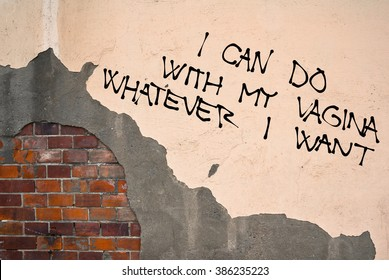 Handwritten graffiti supporting emancipated feminist women sprayed on the wall, anarchist aesthetics